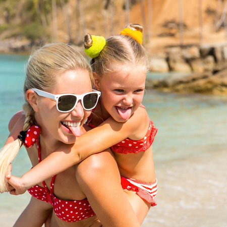 mammy: Beautiful mammy sunglasses with cute little daughter on her back. Two in red bikini. Woman and little lady show tongue and smile. Happy family on the shore. Happy mothers day.