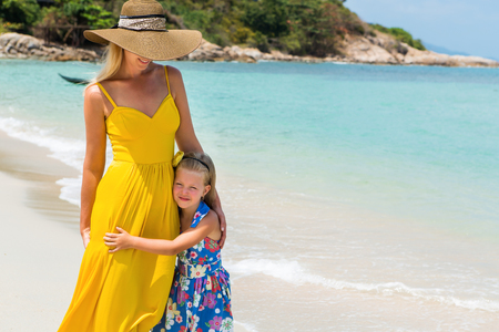 mammy: Beautiful mammy blonde lady in long yellow tunic dress with her pretty little daughter in floral dress at the seaside. Girl hugs her mom and smiles. Happy family on the beach. Happy mothers day.
