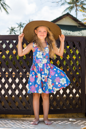 Openluchtportret van leuk klein meisje in bloemenkleding en strandstrohoed. Kleine dame raakt haar grote hoed aan en glimlacht naar de camera. Zonnige zomerdag. Huis met houten omheining bij achtergrond. Moederdag.
