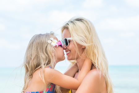 mammy: Outdoor portrait of beautiful blonde mother and her cute daughter. Small girl and her mammy smile and kiss each other. Little lady and her mum wearing sunglasses. Summer sunny day. Happy Mothers day.