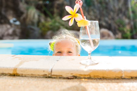 little blonde girl: Cute little blonde girl swimming. Big glass with water, straw and frangipani stay on the pool edge. Little lady looks from pool and look to the camera. Sunbathing and leisure on sunny summer day.