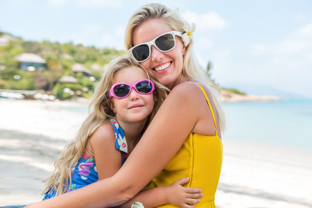 mammy: Outdoor portrait of beautiful blonde mother and her cute daughter. Small girl and her mammy look to the camera on the beach. Little lady and mom wearing sunglasses. Summer sunny day Happy Mothers day. Stock Photo