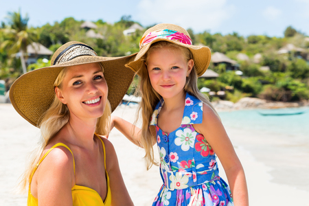 mammy: Close up of a beautiful mammy woman in yellow dress and beach straw hat with her pretty blonde little daughter at tropic seaside. Both smile to camera. Happy family on the beach. Happy mothers day.