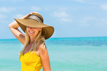 Carefree beautiful fashion blonde woman in beach straw hat and long yellow dress flying in the wind at the tropical beach seashore. Natural woman beauty. Lady hold her hat and smile to the camera.