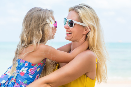 mammy: Outdoor portrait of beautiful blonde mother and her cute daughter. Small girl and her mammy look to each other and smile. Little lady and mom wearing sunglasses. Summer sunny day. Happy Mothers day. Stock Photo