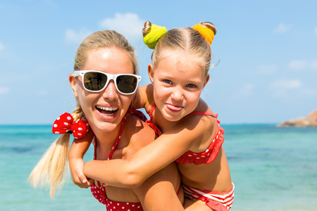 mammy: Beautiful mammy sunglasses with cute little daughter on her back. Two in red bikini. Woman and little lady smile and looking to camera. Happy family on the sea shore. Happy mothers day.