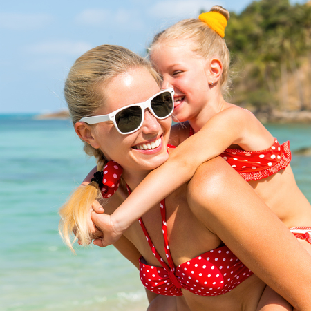 mammy: Beautiful mammy sunglasses with cute little daughter on her back. Two in red bikini. Woman smile and little lady hugging her. Happy family on the sea shore. Happy mothers day. Stock Photo
