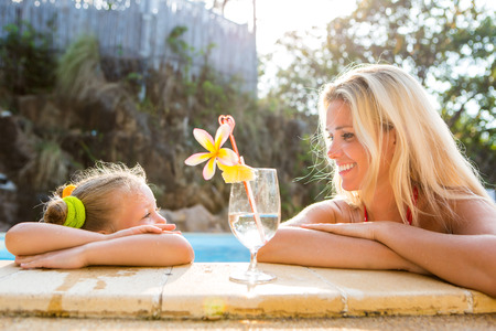 mammy: Outdoor portrait of beautiful blonde mother and her cute daughter. Little girl look to her mammy at the pool. Big glass with water, straw and frangipani stay on the pool edge. Happy Mothers day. Stock Photo