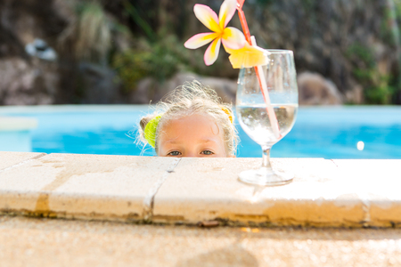 little blonde girl: Cute little blonde girl swimming. Big glass with water, straw and frangipani stay on the pool edge. Little lady peeps from pool and look to the camera. Sunbathing and leisure on sunny summer day. Stock Photo