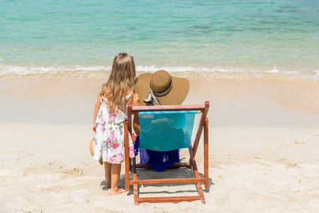 mammy: Beautiful mother lady in dress and beach straw hat with her pretty blonde cute daughter. Mammy sitting in a beach chair. Little lady stand. Happy family on the beach. Happy mothers day. Stock Photo