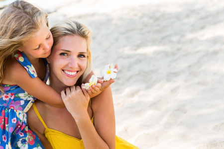 mammy: Outdoor portrait of cute small blonde girl hugging her beautiful mother. Little lady hold frangipani tropical flowers in hands. Her mammy smile to the camera. Summer sunny day. Happy Mothers day.
