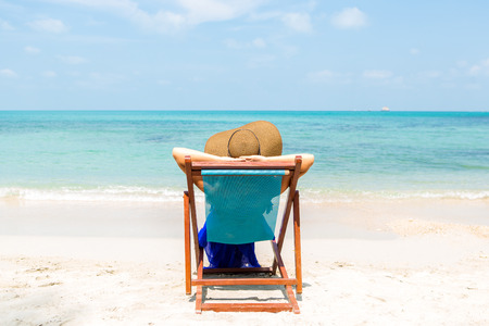 mammy: Beautiful mammy in long blue dress and beach straw hat relaxing in a beach chair. Cute woman relaxing and look to the sea shore. Lady near coastline. Photo from back. Happy mothers day. Stock Photo