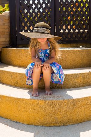wind down: Outdoor portrait of beautiful girl in floral dress and beach straw hat. She sit on stairs and look down. Wind waves her blonde hair. Summer day. Wooden fence at tropical background. Mothers day. Stock Photo