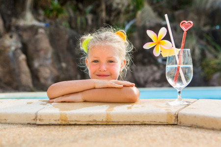 little blonde girl: Cute little blonde girl swimming in big pool. Big glass with water, straw and frangipani stay on the pool edge. Little lady smile and look to the camera. Sunbathing and leisure on sunny summer day.