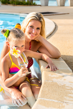 mammy: Outdoor portrait of beautiful blonde mother mother in bikini and her cute daughter in swimsuit. Little girl and her mammy look to the camera. Happy family at the pool. Happy Mothers day. Stock Photo