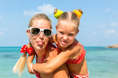 mammy: Beautiful mammy sunglasses with cute little daughter on her back. Two in red bikini. Woman and little lady show tongue, smile and looking to camera. Happy family on the sea shore. Happy mothers day.