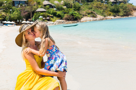 mammy: Close up of a beautiful mother female in yellow dress and beach straw hat with her pretty blonde little daughter at seaside. Girl kiss her mammy. Happy family on the beach. Happy mothers day.