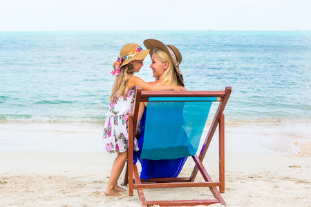 mammy: Beautiful mother woman in dress and beach straw hat with her pretty blonde cute daughter. Mammy sitting in a beach chair. Little lady stand. Happy family on the beach. Happy mothers day. Stock Photo