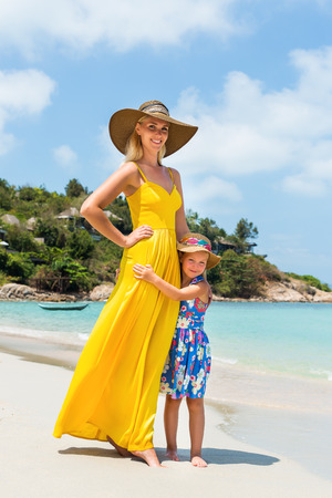 mammy: Beautiful mammy lady in long yellow tunic dress with her pretty blonde little kid in floral dress at the seaside. Girl hugs her mum and smiles. Happy family on the beach. Happy mothers day. Stock Photo