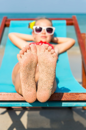 Leuk meisje in rood badpak en een zonnebril te genieten op een ligstoel rust op het strand stoel op tropisch strand oceaan kust. Zonnebaden en ontspanning op zonnige dag. Nadruk op haar voeten in het zand. Stockfoto
