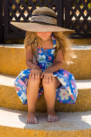 wind down: Outdoor portrait of little cute girl in floral dress and beach straw hat. She sit on stairs and look down. Wind waves her blonde hair. Summer day. Wooden fence at tropical background. Mothers day. Stock Photo