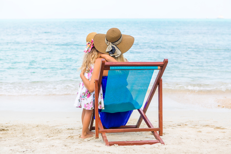 mammy: Beautiful mother lady in dress and beach straw hat with her pretty daughter. Mammy sitting in a beach chair. Little lady stand. They look to the horizon. Happy family on the beach. Happy mothers day. Stock Photo