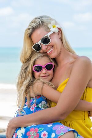 mammy: Outdoor portrait of beautiful blonde mother and her cute daughter. Small girl hugging her mammy on the beach. Little lady and mom wearing sunglasses. Summer sunny day. Happy Mothers day.