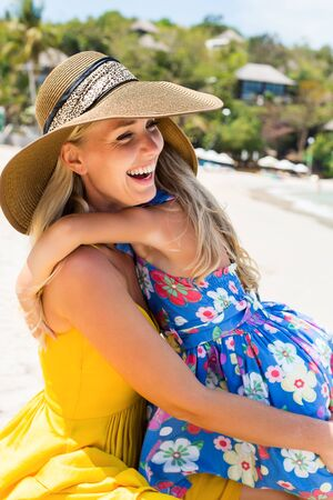 mammy: Closeup of a beautiful mammy woman in yellow dress and beach straw hat with her pretty blonde little daughter at the tropic seaside. Girl hugs her mother. Happy family on the beach. Happy mothers day.