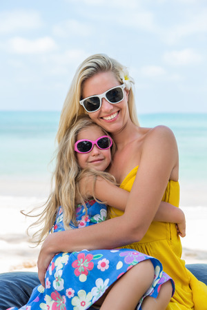 mammy: Outdoor portrait of beautiful blonde mother and her cute child. Small girl hugging her mammy on the beach. Little lady and mom wearing sunglasses. They smiling. Summer sunny day. Happy Mothers day.