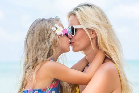 mammy: Outdoor portrait of beautiful blonde mother and her cute daughter. Small girl and her mammy smile and kiss each other. Little lady and mom wearing sunglasses. Summer sunny day. Happy Mothers day.