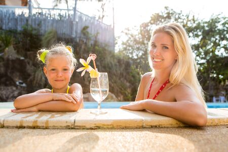 mammy: Outdoor portrait of beautiful blonde woman mother and her cute daughter looking to the camera. Little girl and mammy at the pool. Glass with water and frangipani stay on pool edge. Happy Mothers day. Stock Photo