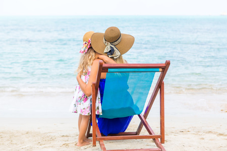 mammy: Beautiful mother lady in dress and beach straw hat with her pretty daughter. Mammy sitting in a beach chair. Little lady stand. They look to the water. Happy family on the beach. Happy mothers day.