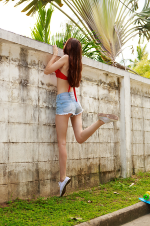 teen bikini: Pretty beautiful girl in red bra bikini, trendy sunglasses and short denim shorts trying climb up a stone wall. Urban scene, city life. Cute attractive sexy hipster lady look over high fence. Stock Photo