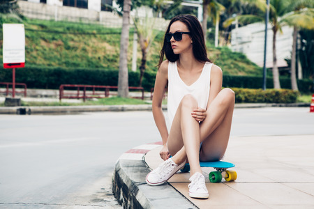girl in jeans: Portrait of slim young beautiful girl in white t-shirt, short jeans shorts and trendy sunglasses sit on blue penny skateboard. Urban scene, city life. Cute attractive sexy hipster woman have fun. Stock Photo