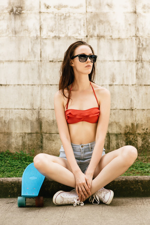 teen bikini: Pretty beautiful girl in red bra bikini, white sneakers, trendy sunglasses and short denim shorts sit cross-legged with short skate board. Urban scene, city life. Cute attractive sexy hipster lady. Stock Photo