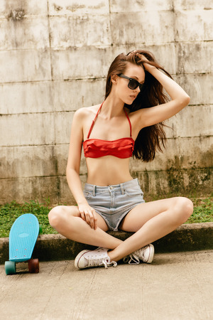 teen bikini: Pretty beautiful girl in red bra bikini, sneakers, trendy sunglasses and short shorts sit cross-legged with short skate board. Urban scene, city life. Cute attractive sexy hipster lady touch her hair.