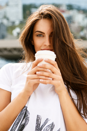 Happy beautiful female cute brunette lady with long healthy hair in front of business sport building hold with two hands paper cup with hot coffee tea and look to the camera. Urban scene, city life.