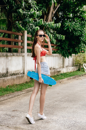 board shorts: Beautiful woman in red bra bikini, white sneakers and short denim shorts walk with blue penny skate board. Urban scene, city life. Cute attractive sexy hipster lady touch her trendy sunglasses. Stock Photo