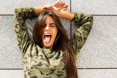 Portrait of happy beautiful woman with long sexy healthy hair in khaki top and ripped jeans with wooden longboard skateboard show tongue to the camera and smile. Urban scene, city life. Hipster lady. Stock Photo