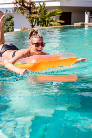 swimming race: Happy beautiful woman in trendy swimsuit and sunglasses have fun at hotel swimming pool party. Young sexy girl enjoying holiday, smiling, having fun and win swimming race on inflatable orange mattress.