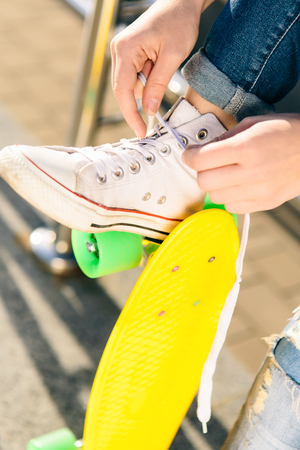 Close up of sexy lady with penny board skateboard in jeans and white sneakers sit on railings and untying laces. Modern urban hipster girl have fun. Good sunny summer day for lifestyle skateboarding. Stock Photo