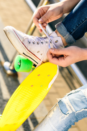 Close up of sporty woman with penny board skateboard in jeans and white sneakers sit on railings and tying laces. Modern urban hipster girl have fun. Good sunny summer day for lifestyle skateboarding.