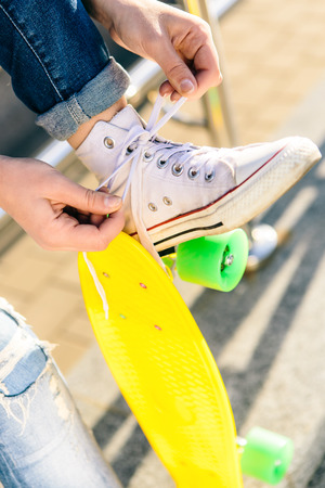 Close up of sporty lady with penny board skateboard in jeans and white sneakers sit on railings and tying laces. Modern urban hipster girl have fun. Good sunny summer day for lifestyle skateboarding.