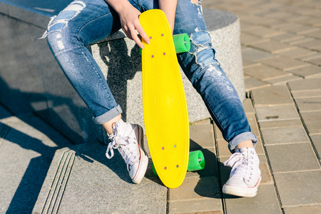 Close up of slim lady legs in jeans and white sneakers. She sit and hold penny board skateboard. Modern urban hipster girl have fun. Good sunny summer day for lifestyle skateboarding and have fun. Imagens