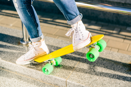 Close up of ladys legs in jeans and white sneakers on penny board skateboard. Sit on railings and have fun. Modern urban hipster girl have fun. Good sunny summer day for lifestyle skateboarding.