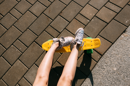 extreme close up: Close up of long lady leg in white sneakers resting after extreme funny ride her penny board skateboard. Modern urban hipster girl have fun. Good sunny summer day for skateboarding and have fun.