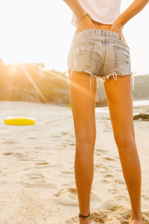 Close up of legs of a beautiful fit lady in white shirt and denim shorts near big inflatable ring. She hold hands on her back. Beauty sunshine cute girl on a tropical sand beach with large stones. Reklamní fotografie