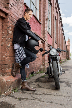 brutal: Close-up of a handsome rider biker guy hand with black helmet near brick wall and classic style cafe racer motorcycle. Bike custom made in vintage garage. Brutal fun urban lifestyle. Outdoor portrait. Stock Photo