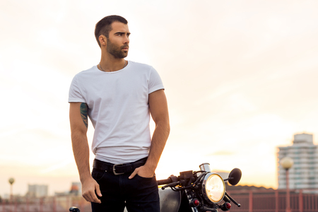 Sporty biker handsome rider male in white blank t-shirt walk away from classic style cafe racer motorbike at sunset. Vintage bike custom made in garage. Brutal urban lifestyle. Outdoor portrait. Stock Photo