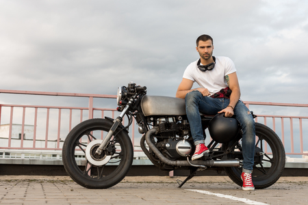 クラシックなスタイルのバイカー カフェ レーサー バイクの上にひげと口ひげ座るとハンサムなライダー男とガール フレンドの待つ。バイク カスタ 写真素材